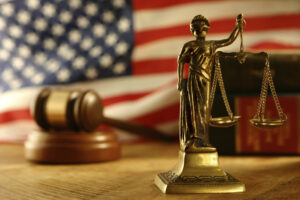 Immigration: Lady scales of Justice in front of the American flag and a gavel